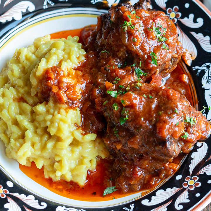 Delicious pressure cooker oxtail stew along a side of saffron rice on a black and white Italian dish.