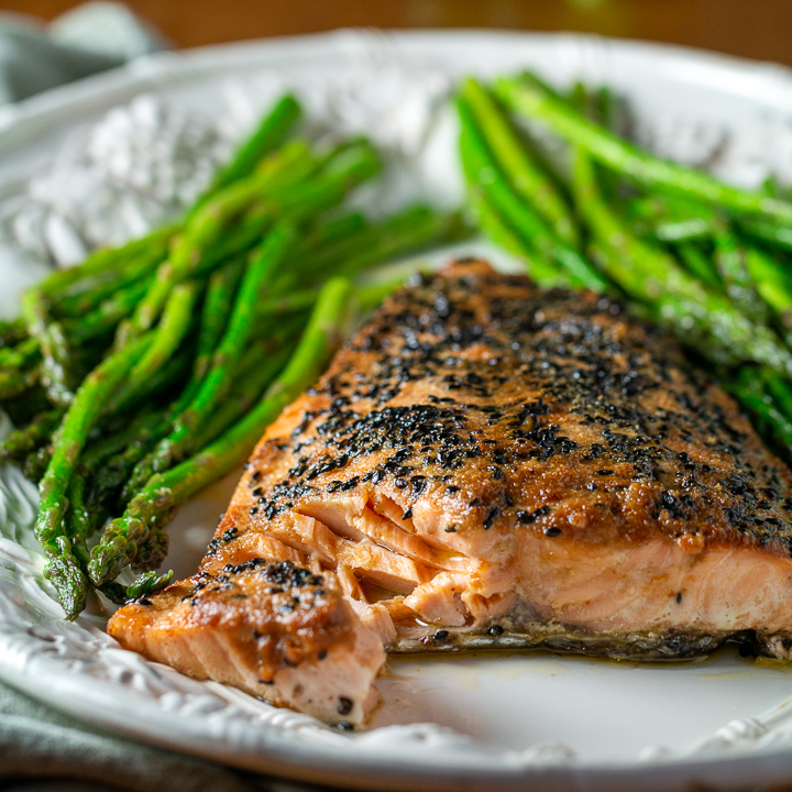 Baked miso salmon with asparagus on a white plate.