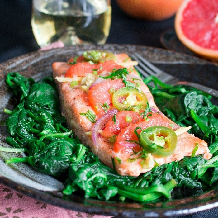 Spicy Citrus Baked Salmon on a bed of spinach that was cooked in parchment paper.
