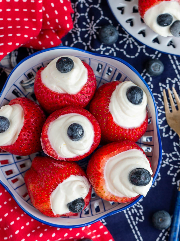 Cheesecake stuffed strawberries on a old fashion white and blue plate.