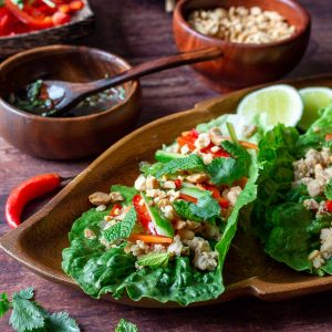 Healthy chicken lettuce wrap topped with fresh vegetables, herbs, roasted peanuts of a wooden plate with prik nam pla sauce next to it.