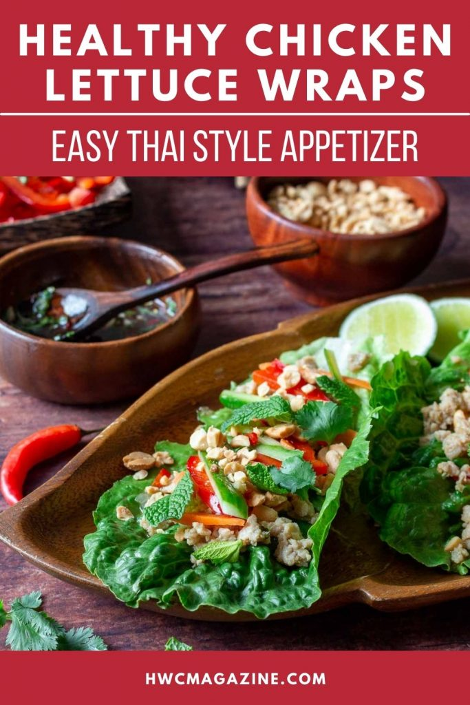 Thai style chicken lettuce wraps on a wooden board with prik nam pla sauce and peanuts on the side.