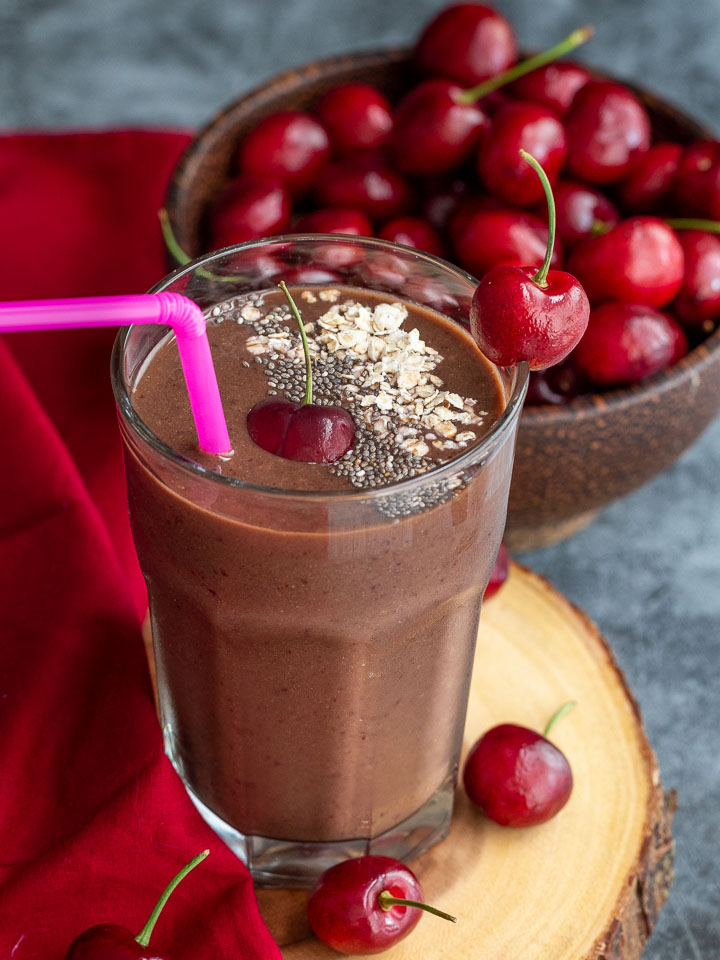 Big  bowl of red cherries with a Mexican Chocolate cherry smoothie ready to drink..