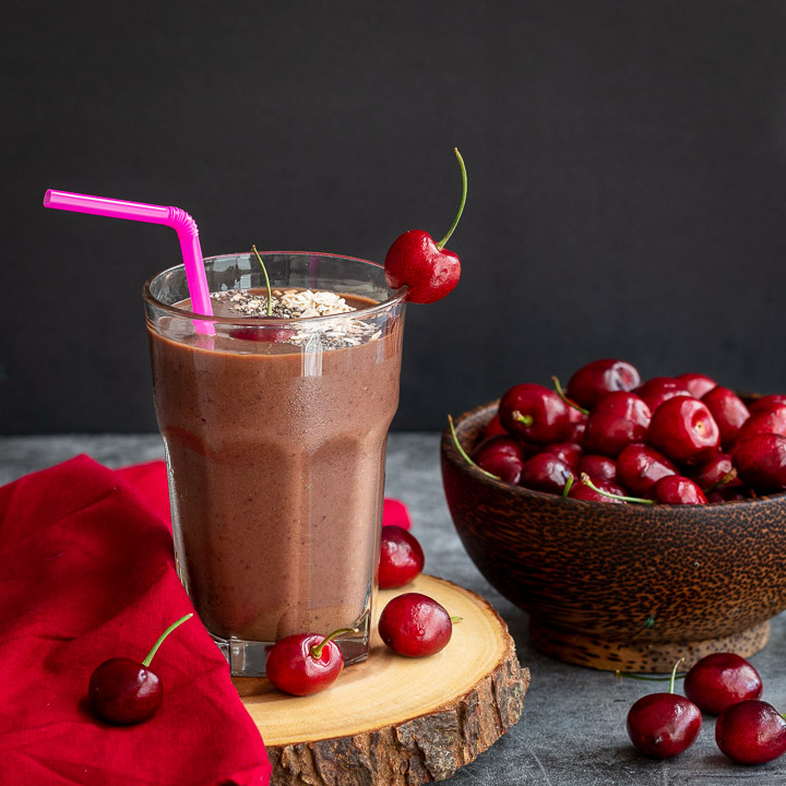 Chocolate Cherry smoothie on a wooden serving tray garnished with fresh cherries.