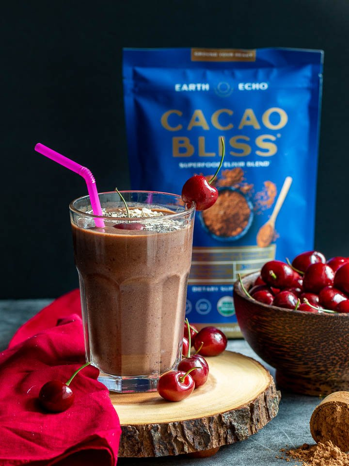 Cacao powder on display with cherries and a smoothie.