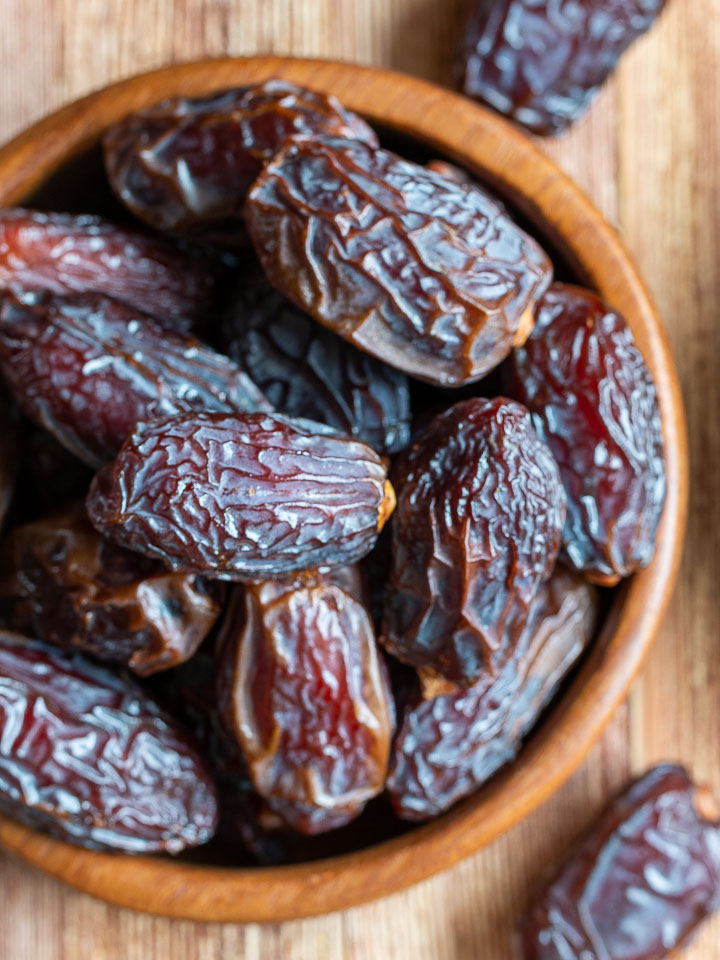 Whole Medjool dates in a wooden bowl.