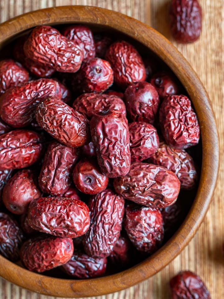 whole Red dates (Jujubes) in a wooden bowl.) in a