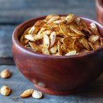 Cajun air fryer pumpkin seeds in a wooden bowl.